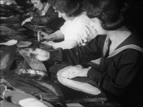 b/w 1910s female factory workers pasting fabric pieces together making footballs / documentary - 1910 stock videos & royalty-free footage