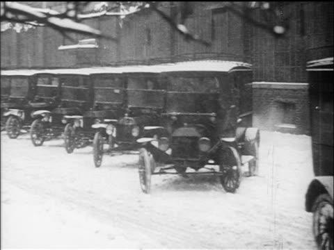 vidéos et rushes de b/w 1910s fleet of trucks driving off in snowstorm / documentary - véhicule utilitaire léger