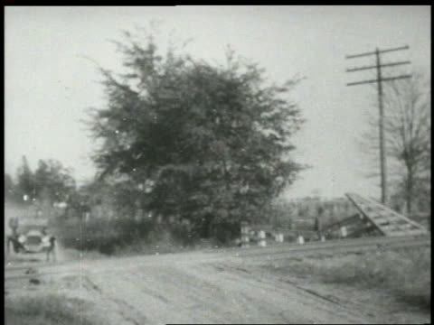 b/w 1910s ford model t speeding over train tracks toward + past camera / car jumps off ground - フォード・t型モデル点の映像素材/bロール