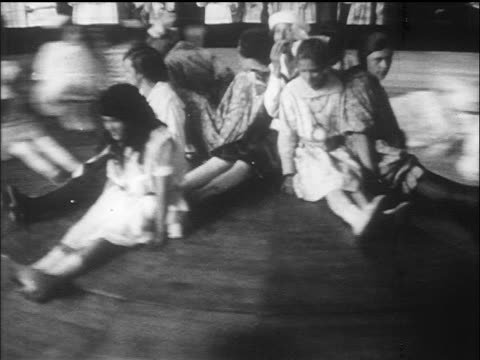 stockvideo's en b-roll-footage met b/w 1910s girls sitting on roulette wheel ride / coney island, nyc / documentary - 1915