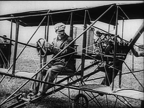 b/w 1910s glenn curtiss sitting in early airplane with man starting engine - 発明家点の映像素材/bロール