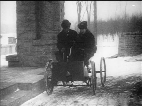 b/w 1910s henry ford and wife clara driving up to house in early car quadricycle / documentary - 発明家点の映像素材/bロール