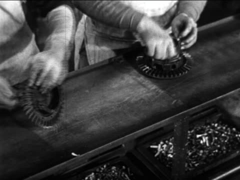 b/w 1910s high angle close up hands of auto workers work on car parts on assembly line / ford factory - ford motor company stock videos and b-roll footage