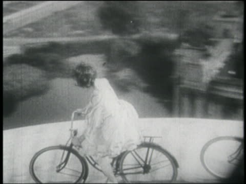 B/W 1910s high angle PAN couple riding bicycles on dome of Palace of Fine Arts / San Francisco