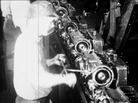 B/W 1910s high angle factory workers work on car engines on assembly line / Ford factory, Highland Park, MI