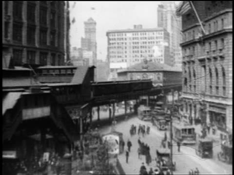 stockvideo's en b-roll-footage met b/w 1910s high angle wide shot elevated train pulling into station above city street / nyc / documentary - 1915