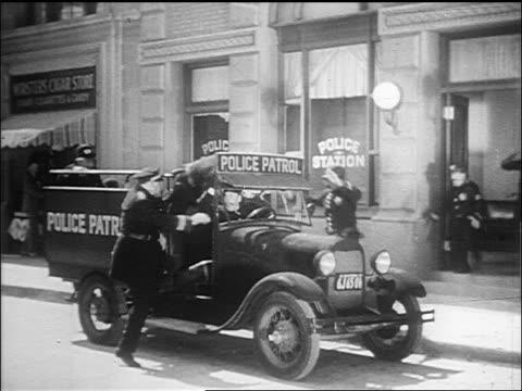 b/w 1910s keystone cops piling into squad car outside stationhouse + drive off / film - falla av bildbanksvideor och videomaterial från bakom kulisserna