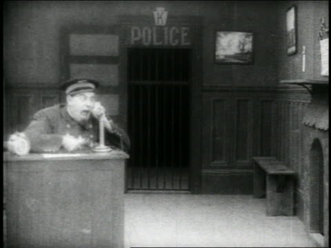 b/w 1910s keystone kops saluting + filing past dispatcher (will rogers) in police station / feature - shouting stock videos & royalty-free footage