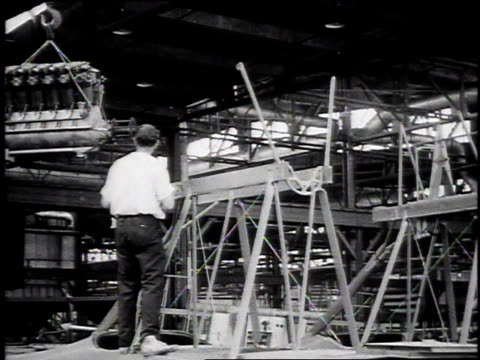 1910s ws liberty engine moving in on pulley and worker grabbing it and lowering it into place / united states - pulley stock videos & royalty-free footage