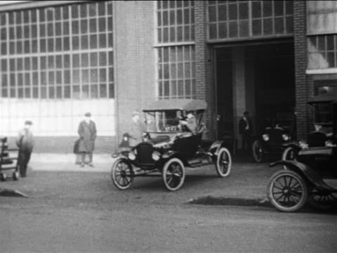 B/W 1910s line of Model T cars exiting factory building / Ford factory / documentary