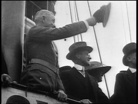 vidéos et rushes de 1910s low angle profile general john pershing waving hat + saluting on ship / surrounded by others - vue en contre plongée