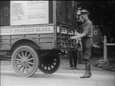 B/W 1910s mail carrier loading packages onto truck / documentary