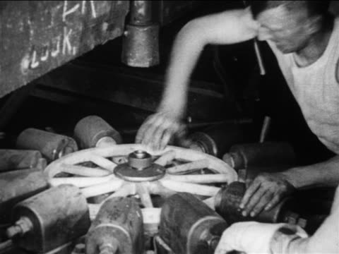 b/w 1910s male factory worker screws wheel together with machine in ford factory / documentary - automobile industry stock videos & royalty-free footage