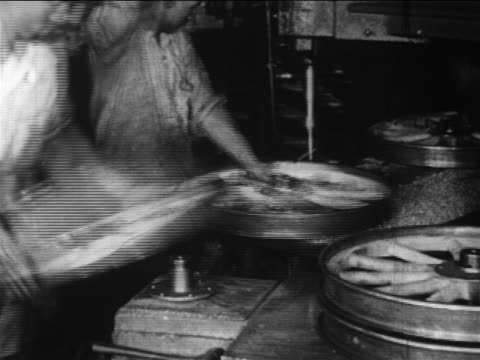 vidéos et rushes de b/w 1910s male factory workers drilling holes in + attaching bolts to wheels / ford factory / docu. - ford