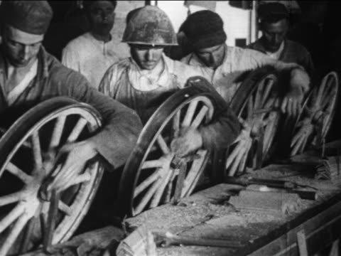stockvideo's en b-roll-footage met b/w 1910s male factory workers sand wooden weel spokes by hand / ford factory / highland park - assemblagelijn