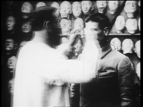 b/w 1910s man attaches prosthetic mask to world war i veteran with severely disfigured face / newsreel - ferito video stock e b–roll