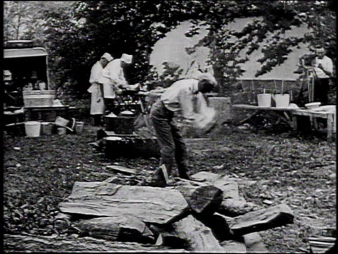 1910s pan man chopping wood at a campsite / united states - フォード・t型モデル点の映像素材/bロール