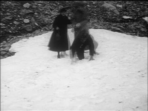 b/w 1910s man falling into crevice in snow as others try to help him out / glacier national park - falla av bildbanksvideor och videomaterial från bakom kulisserna