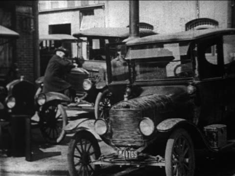 b/w 1910s man getting into model t / mechanic in background / documentary - フォード・t型モデル点の映像素材/bロール