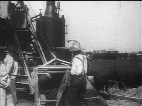b/w 1910s man in overalls emptying contents of wheelbarrow onto large machine / documentary - 1910 stock videos & royalty-free footage