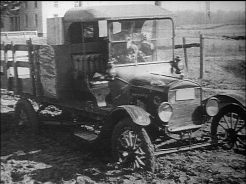 vidéos et rushes de b/w 1910s man in truck trying to get out of mud on road / documentary - véhicule utilitaire léger