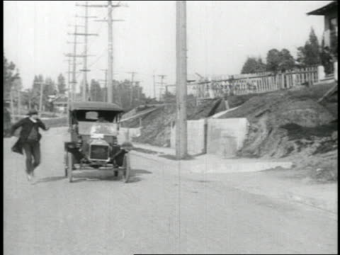 B/W 1910s man running + jumping into moving car / Keystone Kop car in reverse / 3 shots / feature