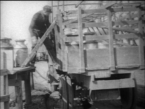 B/W 1910s man unloading pails of milk onto platform from truck / documentary