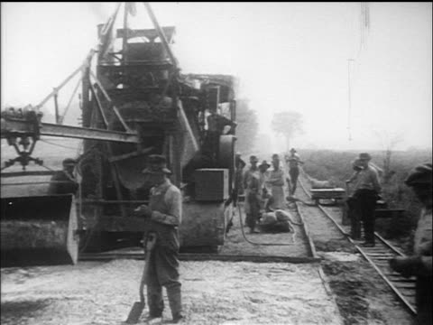 b/w 1910s men in overalls working with shovels / large machine in background (road construction) / documentary - 1910 stock videos & royalty-free footage