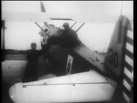 b/w 1910s men loading mail into cockpit of small plane for air mail service / newsreel - 航空便点の映像素材/bロール