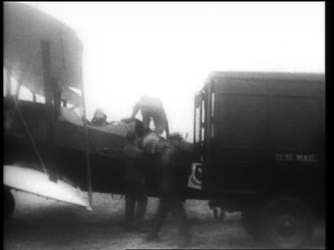 b/w 1910s men loading small plane with mail from u.s. mail truck for early air mail service / newsreel - newsreel stock videos and b-roll footage