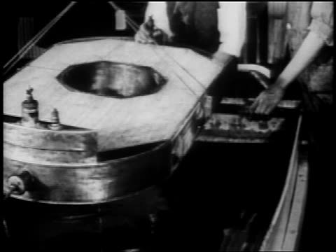 b/w 1910s men lowering airplane part into vat of liquid in warplane factory / wwi - airplane part stock videos and b-roll footage