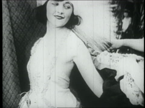 B/W 1910s model removing wrap in fashion show