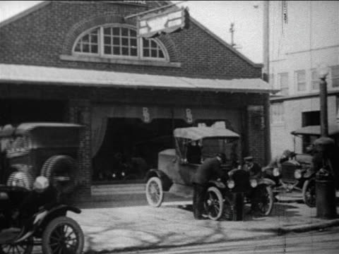 b/w 1910s model t entering car dealership building / men working on cars in front of building / docu - フォード・t型モデル点の映像素材/bロール