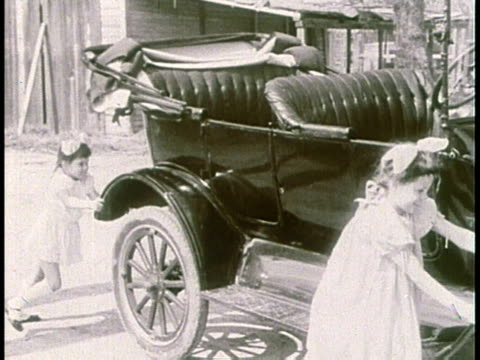 1910s montage children pushing a model t as man tries to start it / united states - フォード・t型モデル点の映像素材/bロール