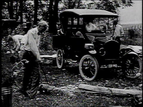 1910s montage warren g harding and harvey firestone chopping wood for a campfire / united states - フォード・t型モデル点の映像素材/bロール
