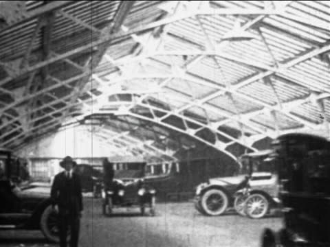 b/w 1910s new cars drive through hangar past camera / ford factory, highland park, mi - ford motor company stock videos and b-roll footage