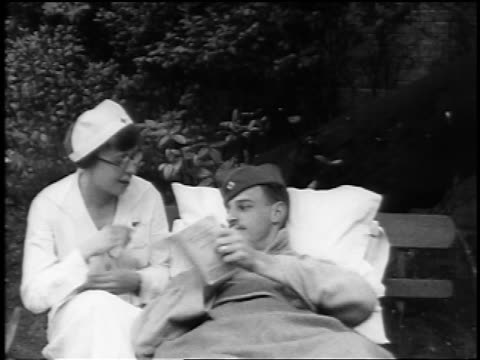 B/W 1910s nurse with eyeglasses reading to wounded soldier lying in bed outdoors / documentary