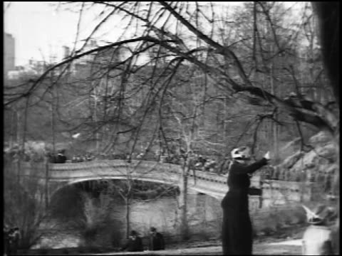 b/w 1910s people crossing footbridge over lake in central park / trees in foreground / nyc / newsreel - newsreel stock videos and b-roll footage