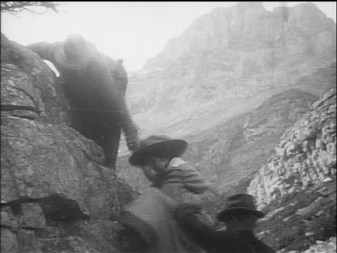 B/W 1910s people rock climbing at Glacier National Park / documentary