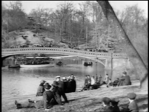 b/w 1910s people sitting on banks + boats on lake with footbridge in central park / nyc / newsreel - newsreel stock videos and b-roll footage