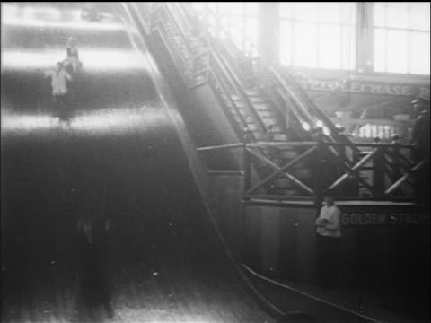b/w 1910s people sliding down giant slide / coney island, nyc / documentary - coney island brooklyn stock videos & royalty-free footage