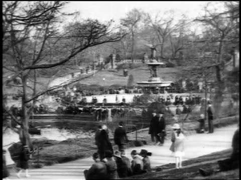 b/w 1910s people walking by bethesda fountain in central park / nyc / newsreel - newsreel stock videos and b-roll footage