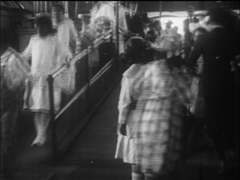b/w 1910s people walking on bouncing walkway in funhouse / coney island, nyc / documentary - coney island stock-videos und b-roll-filmmaterial