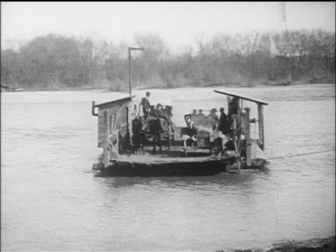 b/w 1910s primitive ferry barge carrying cars across river / documentary - ウマ科点の映像素材/bロール
