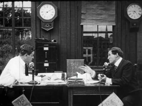b/w 1910s profile 2 men sitting at facing desks put down telephones + talk to each other - 1910 stock-videos und b-roll-filmmaterial