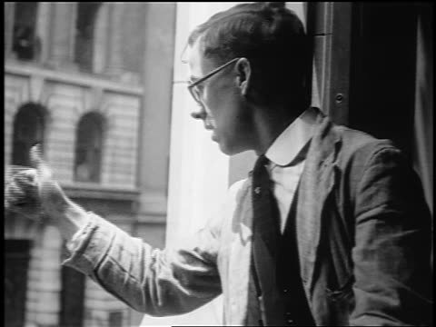 B/W 1910s PROFILE Wall Street broker wearing eyeglasses signaling out of window / NYC