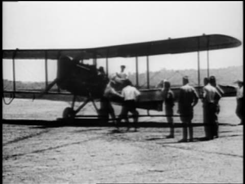 b/w 1910s propeller starting up on warplane preparing for test flight outdoors as men look on / wwi - air vehicle stock videos & royalty-free footage