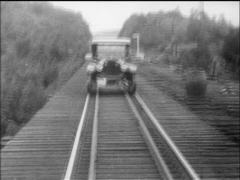 b/w 1910s rear point of view model t driving over train bridge towards camera / documentary - フォード・t型モデル点の映像素材/bロール