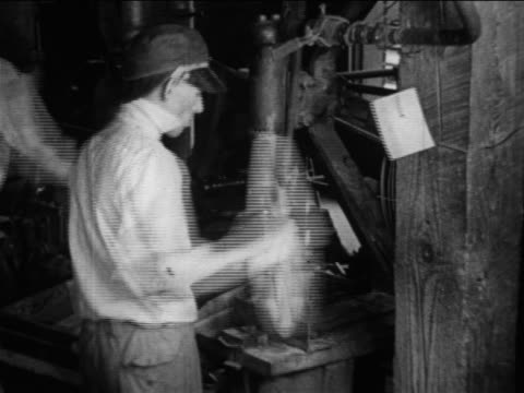 B/W 1910s REAR VIEW factory worker quickly assembles wooden weels / Ford factory / Michigan