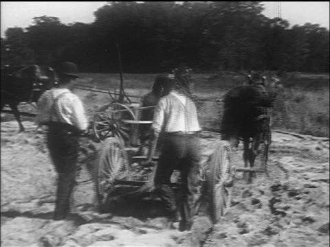 B/W 1910s REAR VIEW farmers driving horses pulling plows / documentary